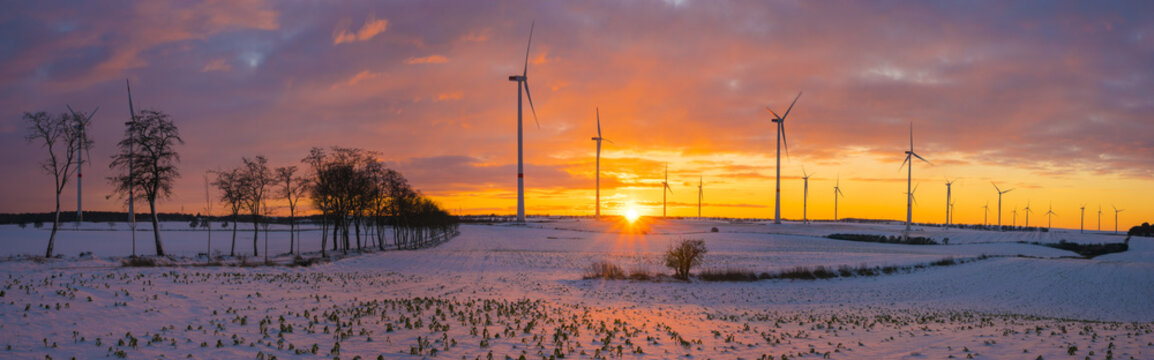 windmills (wind turbines) on the snow-covered field at sunset
