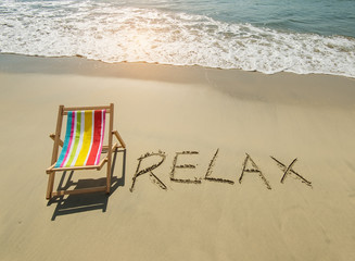 Deck chair with relax written in sand write on tropical beach.