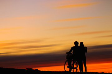 Silhouettes couples and bicycle on sunset sky : silhouette photo