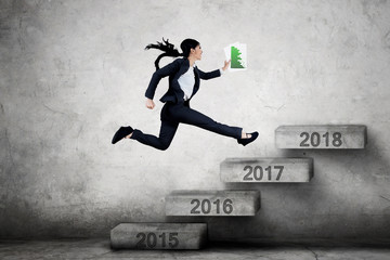 Woman jumping on stairs with financial chart