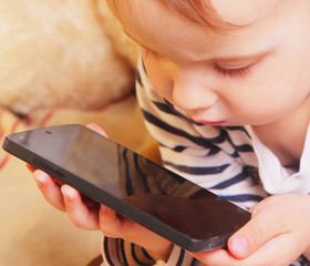 Social Media addiction. beautiful baby girl  holding phone (psyc