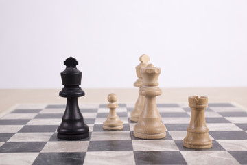 mixed black and white wooden chesspieces on chessboard
