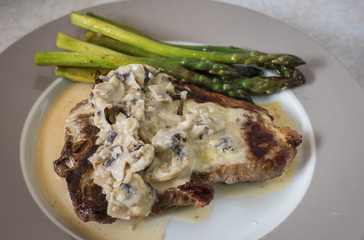 Grilling steak with rosemary, mushroom sauce and asparagus. Fresh, delicious, spicy, juicy meat, healthy.