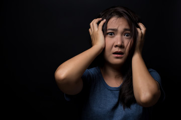 Shocked woman on isolated black background