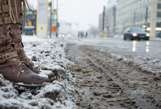 Snow mats and dirty streets in a big city