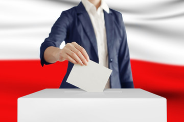 Voting. Woman putting a ballot into a voting box with Poland flag on background.