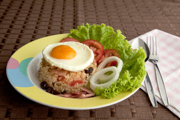 Fry rice with ham , tomato , onion , raisin and egg on top.