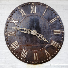 Antique clock face with Roman numerals mounted on wall.