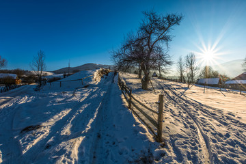 fence on snowy rural field near the village in winter