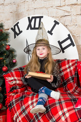 The child, a little girl sitting near a Christmas tree in a witch costume and unwraps a gift.