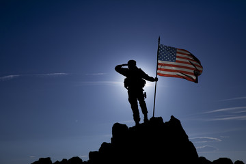 soldier on top of a mountain with a USA flag