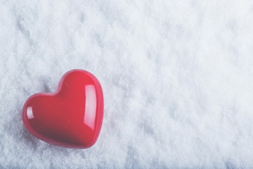 Red glossy heart on a frosty white snow background. Love and St.
