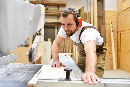 Tischler sägt Holzbrett in einer Schreinerei // Carpenter sawing wooden board in a carpenter's workshop