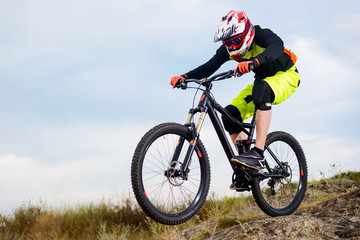 Professional Cyclist Riding the Bike Down Rocky Hill. Extreme Sport Concept. Space for Text.