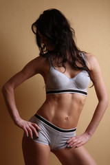 Body slender woman in sportswear standing on the background