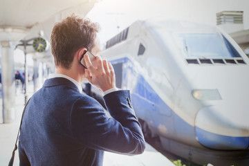 business travel, businessman talking by phone at the railway station while waiting for the train, mobile call