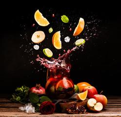 Sangria. Flying fruits. Apple, orange, lime, pomegranate, mint. Drink. Wine. Concept. Dark moody. Spain. Beverage jug. Juice jar.