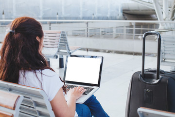woman using laptop computer in the airport, banking online or web check-in, passenger looking at empty blank screen