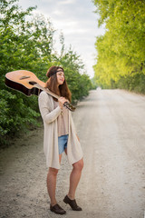 Hippie girl standing on the road with a guitar