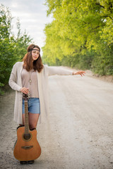 hippie girl with a guitar travels hitchhiking