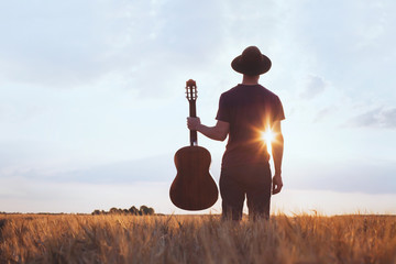 music festival background, silhouette of musician artist with acoustic guitar at sunset field.
