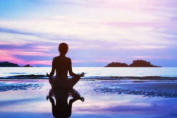 Wall Mural - beautiful yoga background, silhouette of woman meditating on the beach at sunset