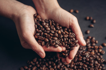 coffee beans, black background, coffee beans in hand