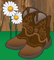 A pair of cowgirl boots is resting by a fence and flowers