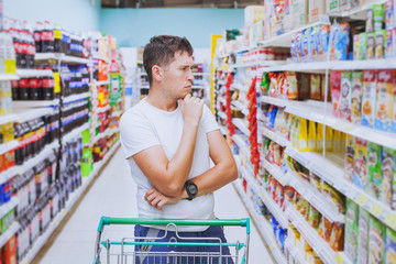 thoughtful man in the supermarket, customer thinking, choose what to buy, choice in shopping