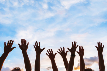 community initiative or volunteering concept, hands of group of people in the sky, silhouette