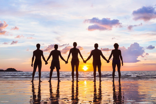 community or group concept, silhouettes of people standing together and holding hands, team on the beach, unity background