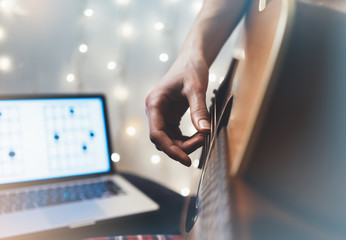 Hipster playing guitar in home atmosphere, person studying on musical instrument, notes in laptop on background glow bokeh Christmas illimination, female hands in holiday on relax glitter decoration