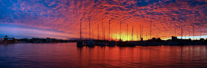 Crimson and Blue marina Sunset with water reflections and boats in silhouette.
