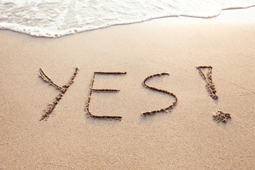 YES concept, positive changes in the life, word written on sand beach.