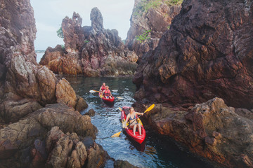 kayaking, adventure travel, group of people on kayaks between cliffs