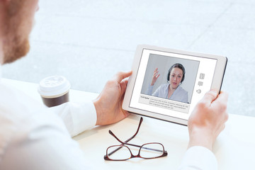 e-learning, video conference, coaching online, man looking at the screen of tablet