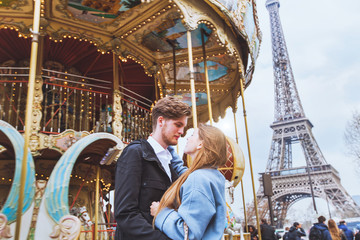 happy couple in Paris, romantic kiss near carousel and Eiffel tower