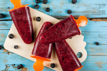 Delicious home-made popsicles of black currant. On a wooden table, top view, copy space