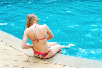 Back view of slim young beautiful woman in colorful swimsuit sitting on the edge of swimming pool. Enjoying tropical holidays