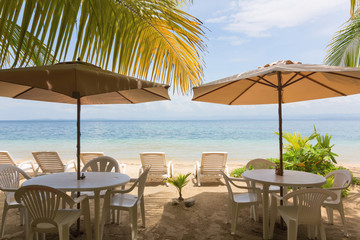 Restaurant tables, sun lounger and beach umbrella under the palm leaves on the beach