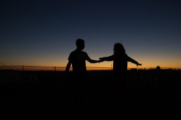 Silhouette couple playing scenario at sunset