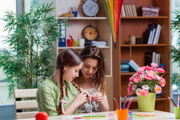 Young girls drawing pictures at home