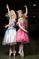 Two young woman cosplayer wearing beautiful dresses posing