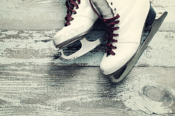 Old white skates for figure skating on a vintage wooden surface