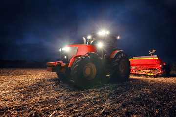 Wall Mural - Tractor preparing land with seedbed cultivator at night