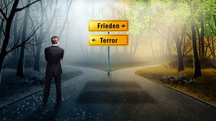 Mann im Anzug steht an Weggabelung zwischen Terror und Frieden