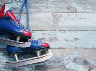 Vintage pair of mens ice skates on an old wooden surface