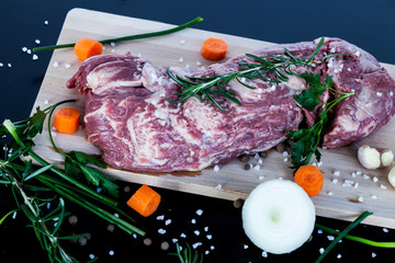 Big piece of raw beef meat with vegetables onion, carrot, garlic and spices pepper, rosemary, parsley, sea salt on a wooden cutting board.