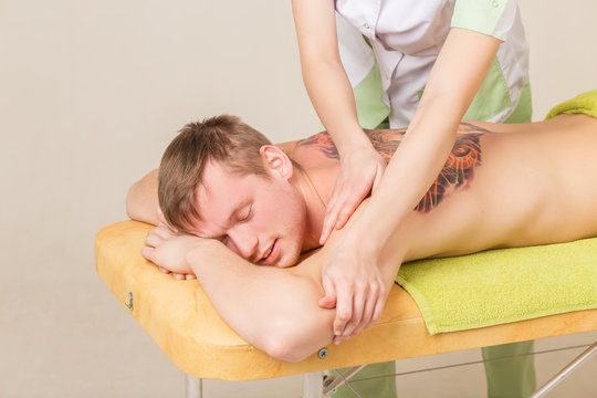 Back massage. Massage therapist massaging lower back region of a