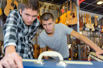 Two young men in musical instrument shop